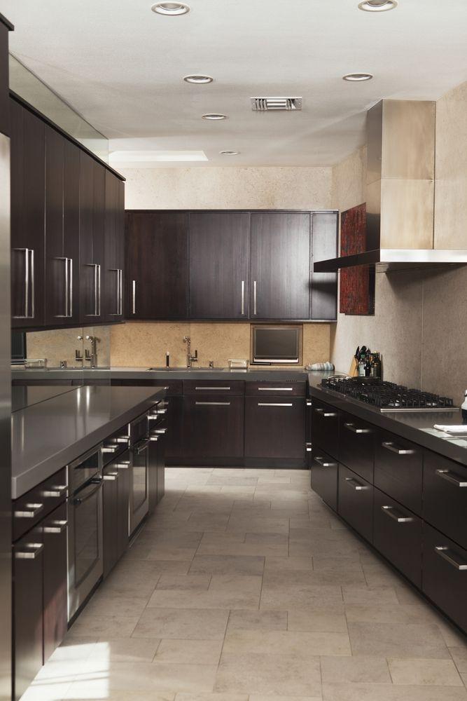 This dark wood galley kitchen combines light beige stone in the ...