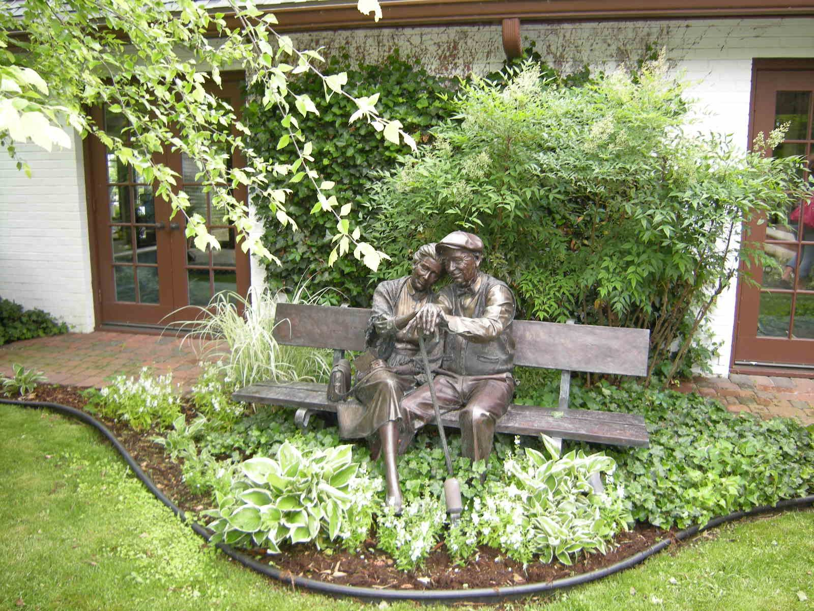 Statue of older couple sitting on a bench Sculptures