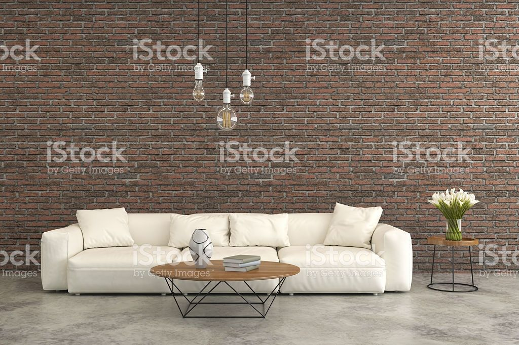 View at a white leather sofa in front of an old brick wall ...