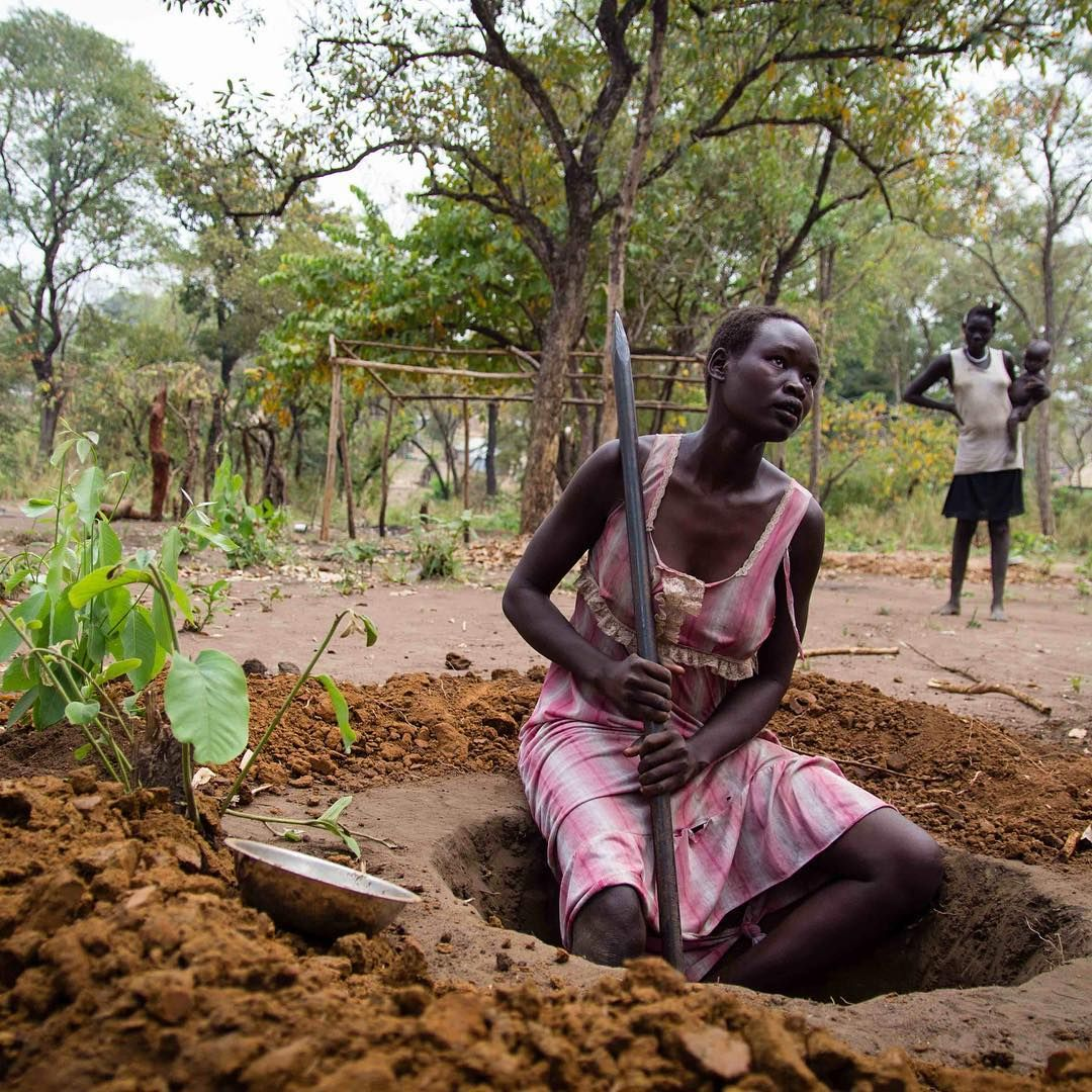 """""""Nyakhoat digs a latrine in a camp for South Sudanese in Gambella, Ethiopia.  She is among 1.8…"""""""