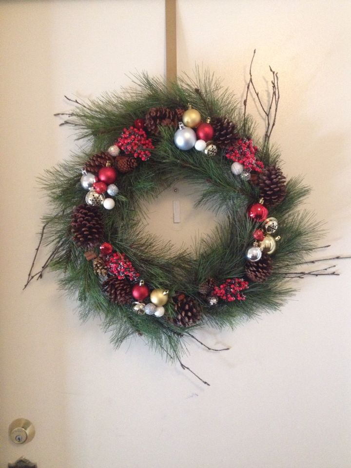 DIY wreath with wire, glue gun, ornaments, bells, pinecones, garland, and wreath frame...turned out great!!