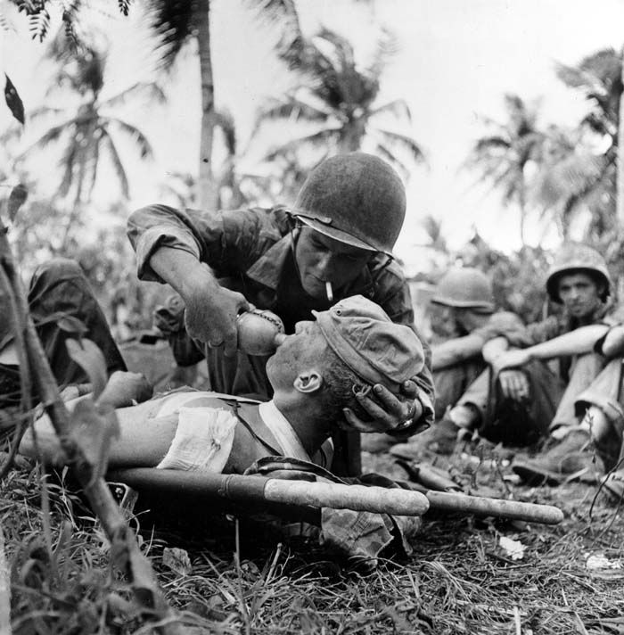 A Navy Corpsman lifts the head of a wounded Marine to give him a sip of water from his canteen as other soldiers relax during a pause in fighting on Guam Island, in the Marianas, in August 1944 during World War II.