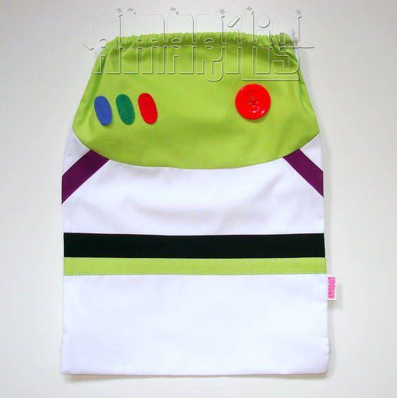 """CRIAÇÃO POR AMARÍLIS ATELIER! <br> <br>Mochila Infantil tipo """"Saquinho"""" com o modelo do Buzz Lightyear <br>Tema Toy Story <br> <br>Macacão de Astronauta na Cor Branca com Detalhes em Verde, Preto e Roxo <br>Aplicações Imitando Botões de Controle <br> <br>Tecido 100% Algodão! <br>Fechamento Prático! <br> <br>PEDIDO MÍNIMO: 12 unidades <br>DIMENSÕES: 34 cm x 24 cm"""