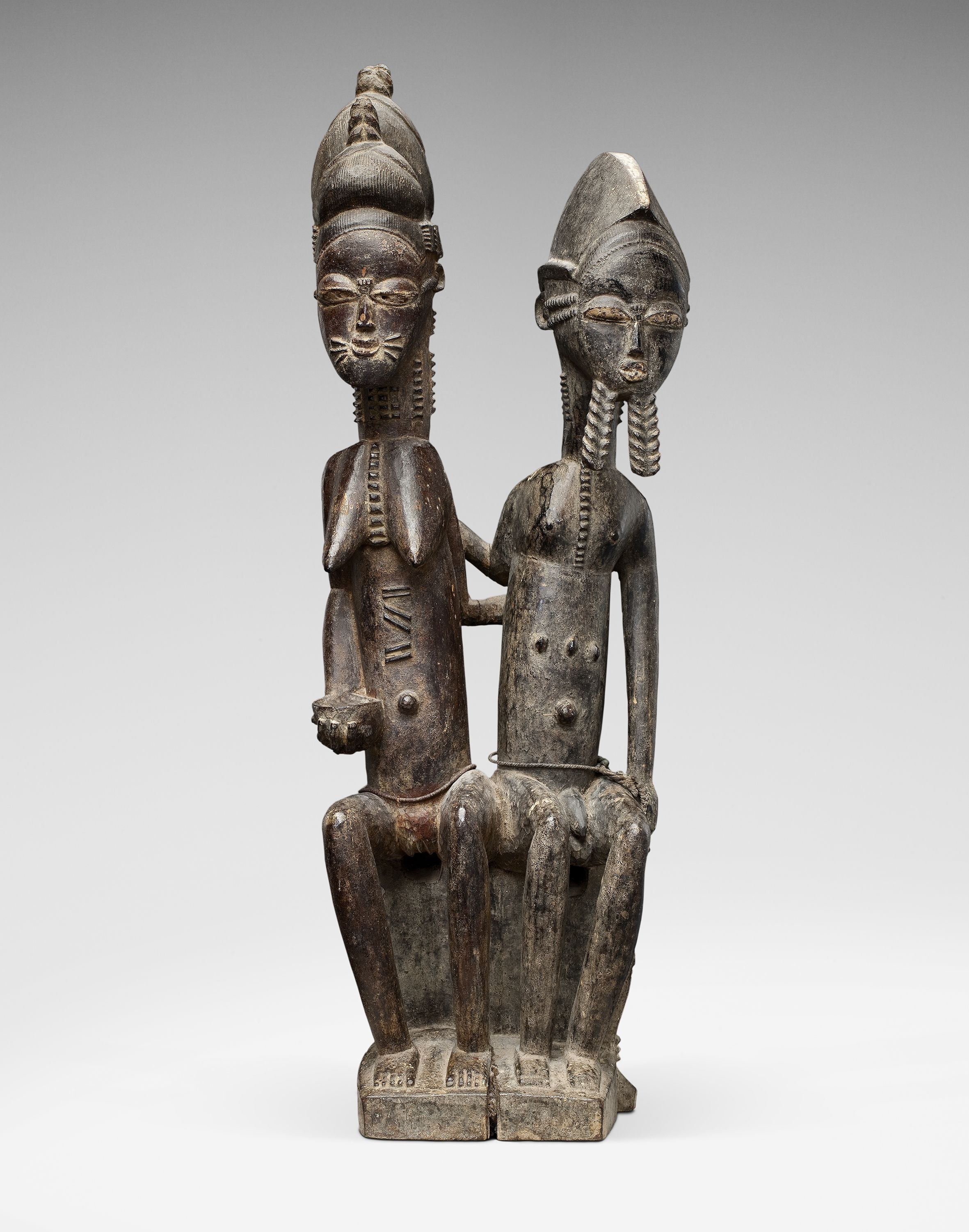 This affectionate seated couple was made by an unknown master in circa 1910. Only five seated Baule couples, carved out of one piece of wood, are known to us. Bernard de Grunne will offer during TEFAF Maastricht 2016 a collection of 18 rare seated statues from the Baule tribe (Central Ivory Coast).
