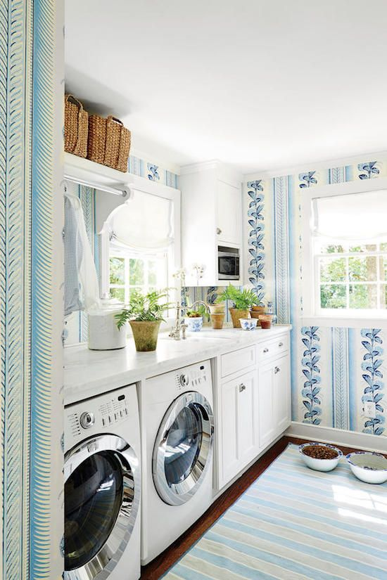 Blue wallpaper in laundry room by Sarah Bartholomew. Because Bartholomew spends so much time in the laundry room, it was important to her that it be pretty. She papered the walls with Quadrille's Climbing Hydrangea and keeps the space filled with plants.