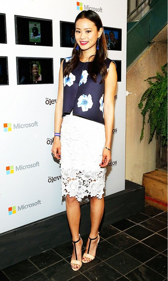 Jamie Chung wears a blue floral top with a white lace skirt, t-strap nude heels, blue earrings, and a gold bracelet.