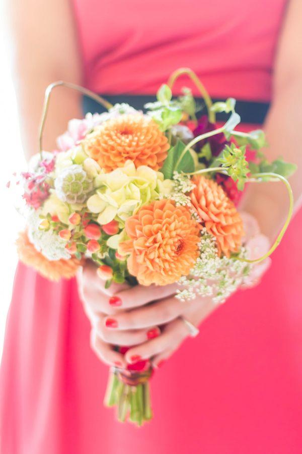 Bold orange bridesmaid bouquet filled with dahlias {Photo by Kim Schepperley via Project Wedding}