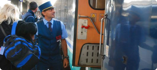 A conductor helping a passenger leave from the train. With ...
