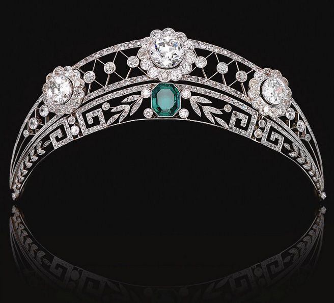 EMERALD AND DIAMOND TIARA, CIRCA 1910, The upper tier of open work trellis design millegrain-set throughout with rose diamonds, and decorated with three flower head cluster motifs set with circular-cut diamonds, the lower tier of foliate and meander design, set with similarly-cut stones and centring on an octagonal emerald. By family tradition it is understood that this tiara was worn at an official dinner given by Kaiser Wilhelm II by an ancestor of the present owner.