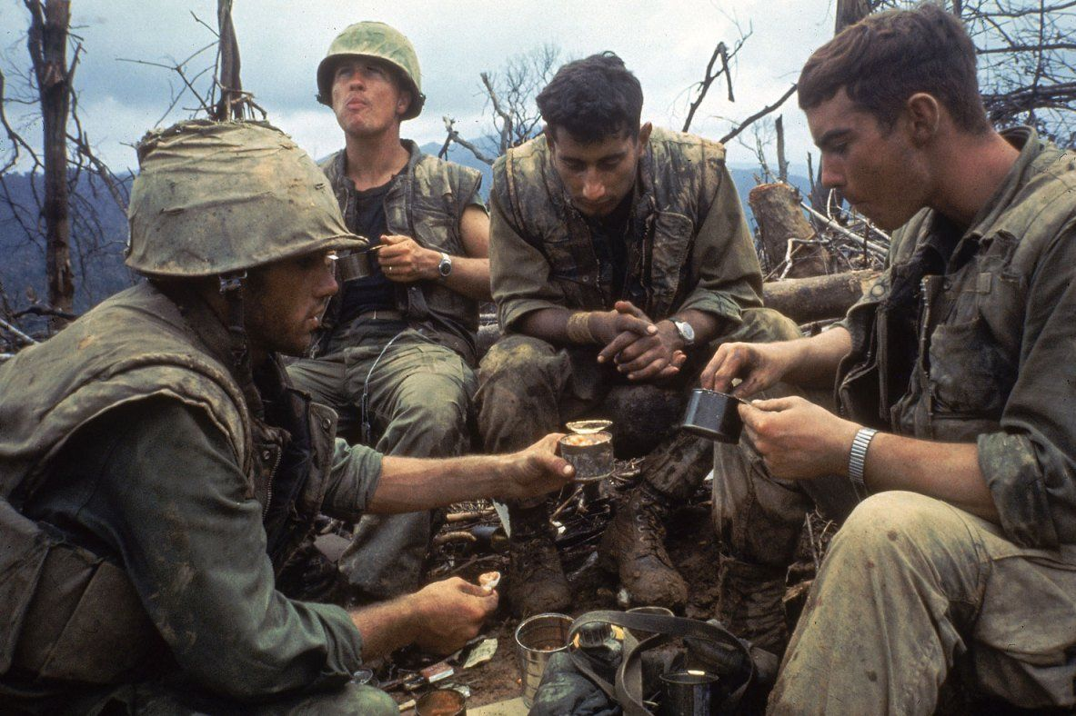 American Marines eat rations during a lull in the fighting near the Demilitarized Zone during the Vietnam War, October 1966.
