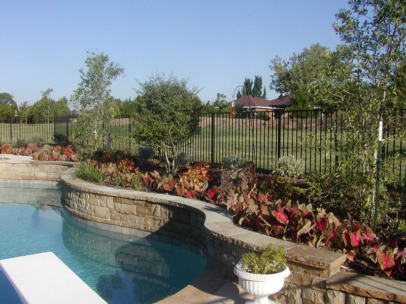 raised bed poolside landscaping with fence