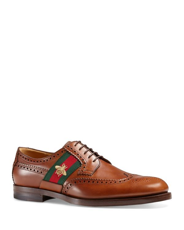 e5e46906e59 Gucci elevates these classic wingtips with a signature stripe detailed with  an embroidered gold bee.