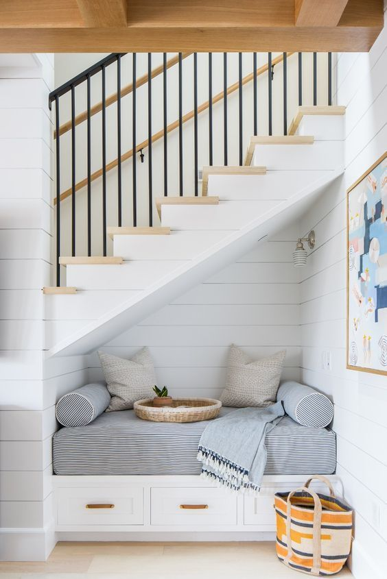 Love this coastal home with reading nook area under the stairs from Brooke Wagner Design #readingnook #coastalliving
