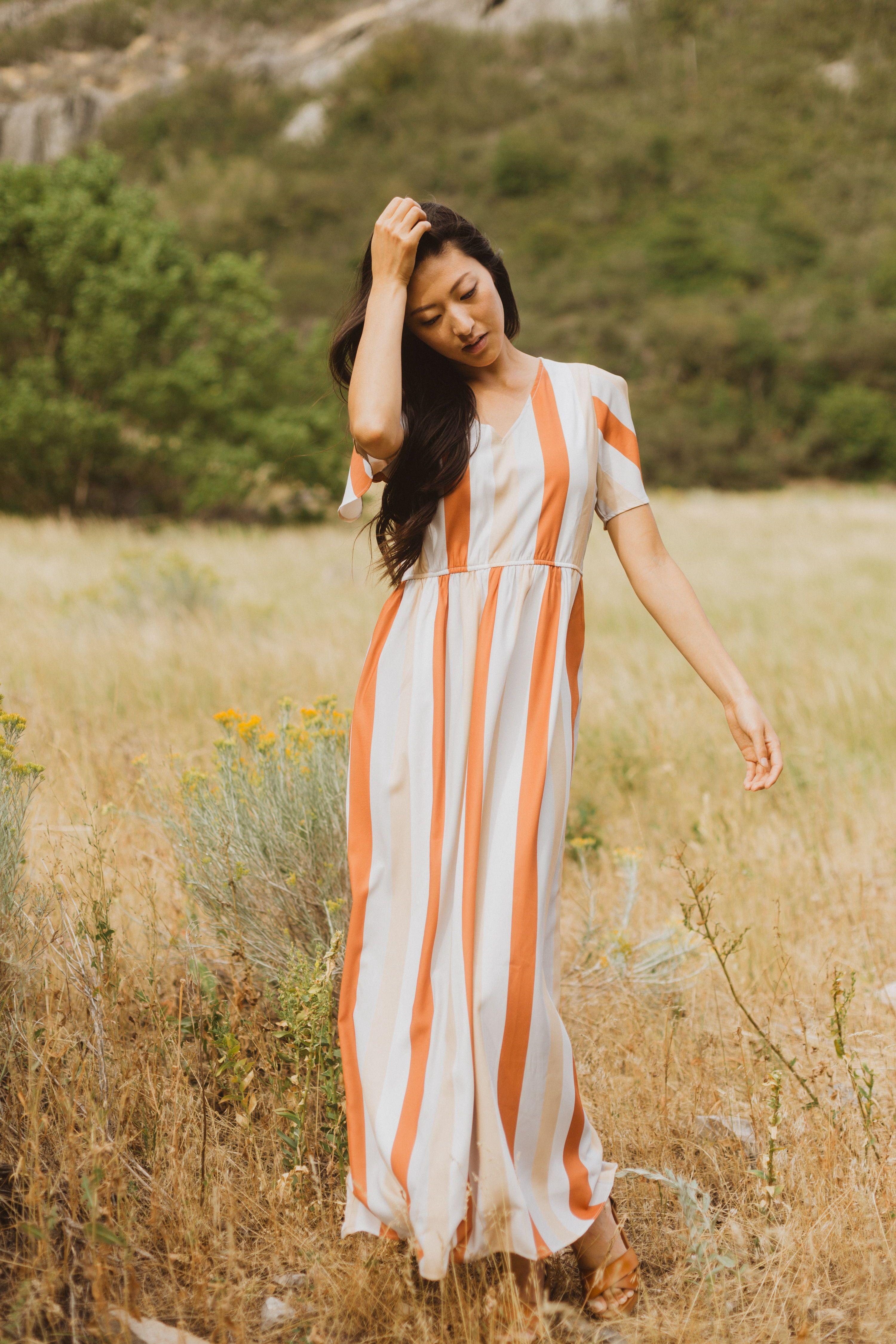 The Butler Striped Maxi Dress Features A Soft V Neckline With Vertical Stripes Down In Pumpkin Pale Peach Against A Neutral C Striped Maxi Fashion Maxi Dress [ 4500 x 3000 Pixel ]