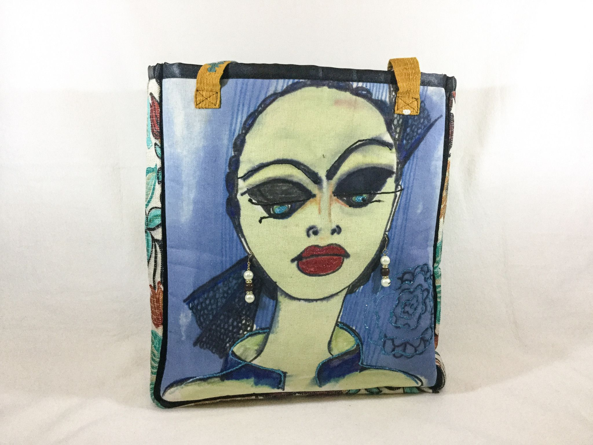"""Melva  So Beautifully Dramatic This bag measures 14"""" wide by 17"""" high by 6"""" deep The image is painted and dyed on linen Melva is wearing faux pearl and purple bead drop earrings The back and sides are a floral tweed-like fabric in teal and orange The inside is lined in a nice stripe print  A 5"""" x 7"""" open side pocket All seams are tailored with pretty black ribbon 9"""" multi-colored woven straps"""