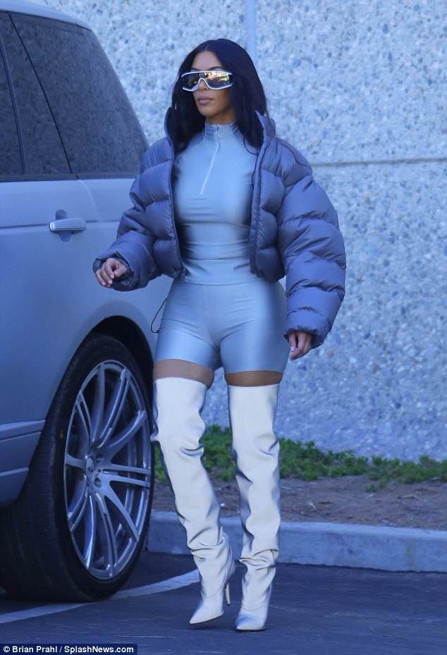 Kim Kardashian shines in silver thigh-high boots and clinging bodysuit
