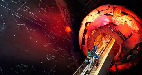 """Feel the power of the planet in this dramatic and atmospheric introduction to the Red Zone... A giant metallic globe presides over the Earth Hall.  Visitors can ascend the globe escalator to the Red Zone's upper galleries. Surrounding it the towering walls, adorned with a celestial map, put our planet in its heavenly context."""