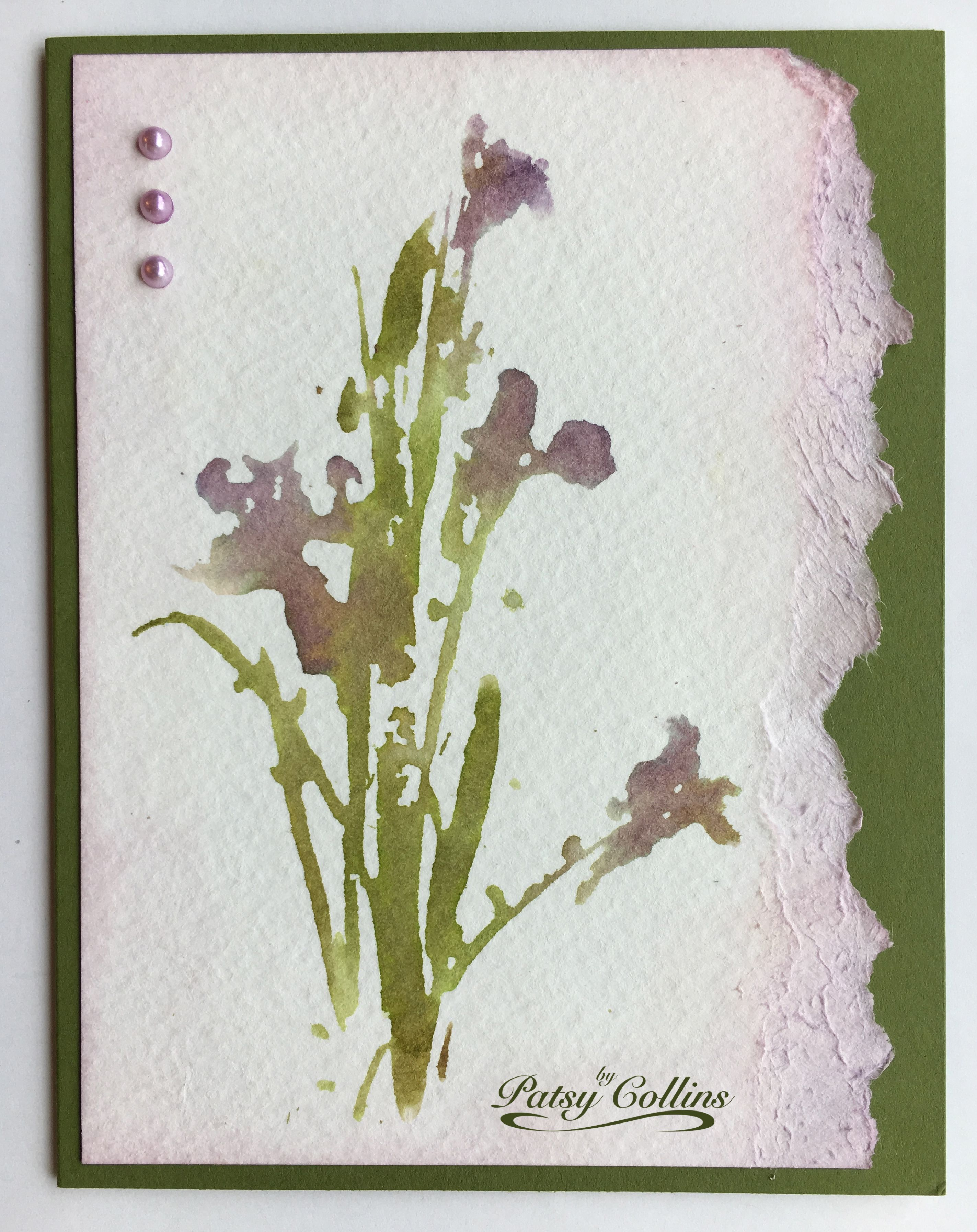"By Patsy Collins. Second generation stamping. Use corners of Distress ink pads to ink ""Irises"" (Penny Black). [milled lavender, dusty concord, peeled paint, forest moss] Spritz stamp with water; stamp onto watercolor paper; save for another card. Spritz stamp again without re-inking. Stamp onto watercolor paper; use for this card. Tear right edge. Use blending tool to apply milled lavender ink on edges. Cover image with hand; spritz torn edge. Add pearls colored with Copic markers."