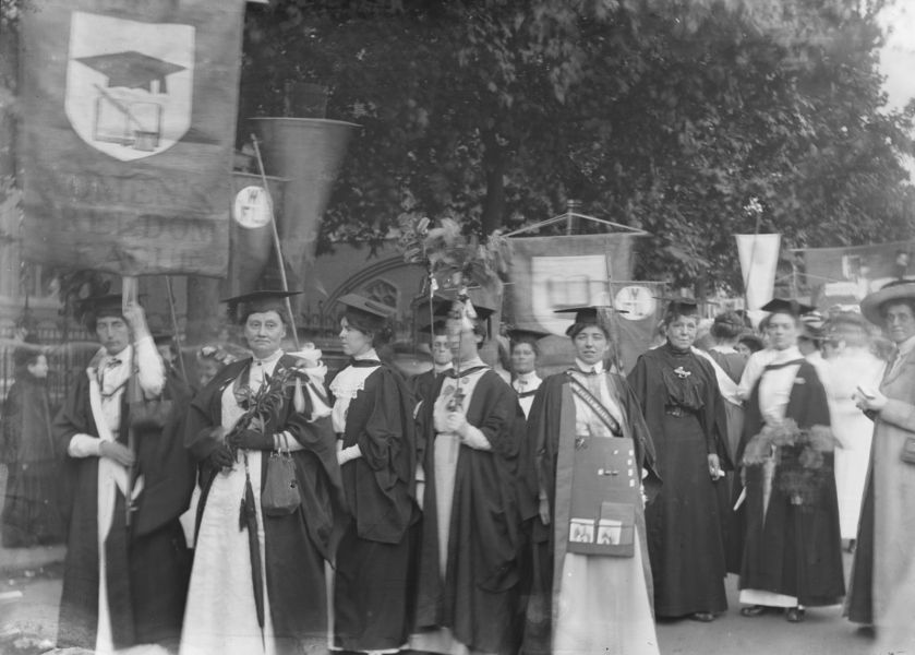 A suffragette procession with women dressed in mortar