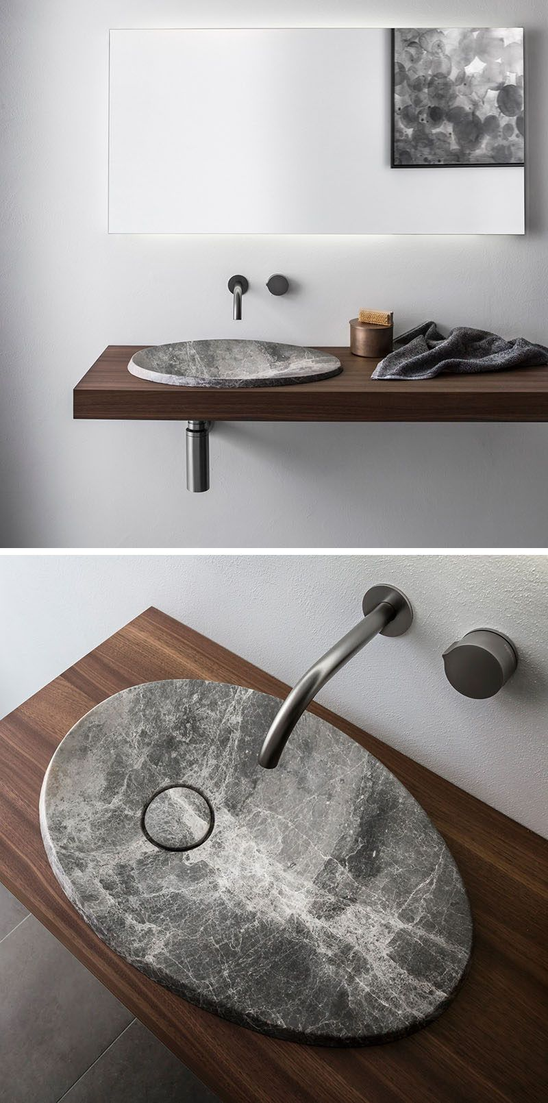 This modern bathroom sink made from natural stone sits on a floating wood vanity and has a simple stainless steel faucet