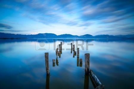 Wooden pier or jetty remains on a blue lake sunset and cloudy sky reflection on water  Long exposure, Versilia Massaciuccoli Lake, Tuscany, Italy  Stock Photo