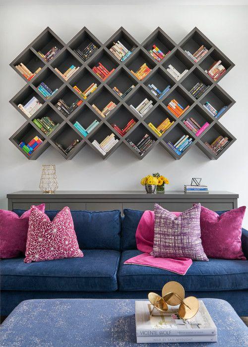 O cinza predomina no ambiente, e está presente na lareira de porcelana, que também serve de suporte para a TV, e nos armários. Mas o destaque é a estante geometrica. Os livros foram organizados por cor, e combinam com o visual divertido da sala.