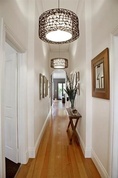 Narrow Hall Table, Matching Frames, And Repeating Light Fixtures.
