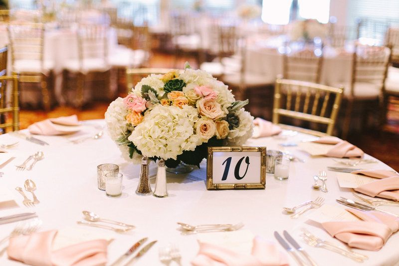 One of two tablescapes at this classic reception, a mercury glass compote filled with hydrangea, creamy blush spray roses, pink ranunculus, succulents and dusty miller is surrounded by mercury glass votives and a gold framed table number.