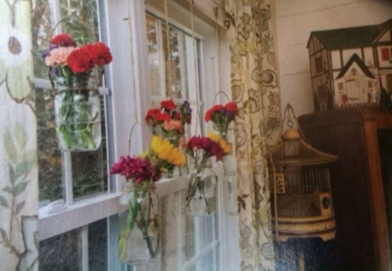 Hang flowers or candles off hooks in front of window. Easy way to add color and essence.