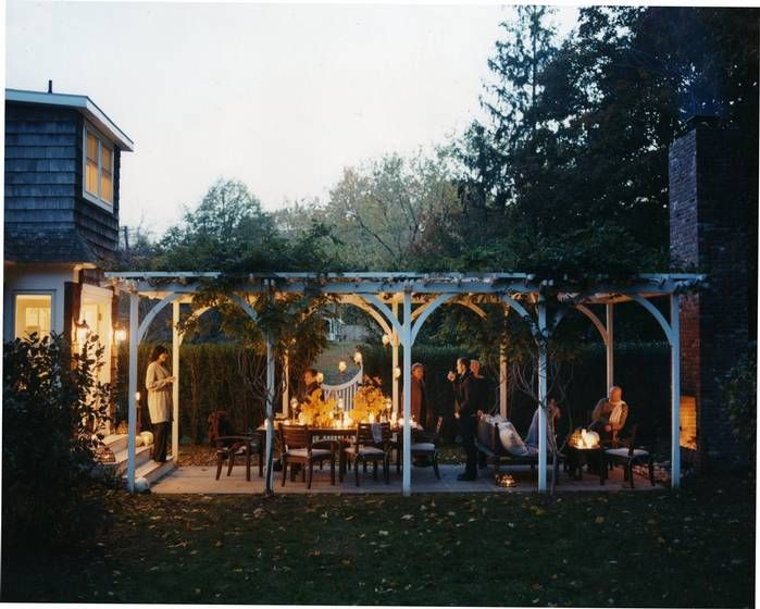 Garden eating area, overhead pergola, with fireplace and seating. Note the Tall hedge that screens and adds privacy, and the nice gate. 1904 Farm House Renovation That Features Very Lovely Black and White Interior | DigsDigs