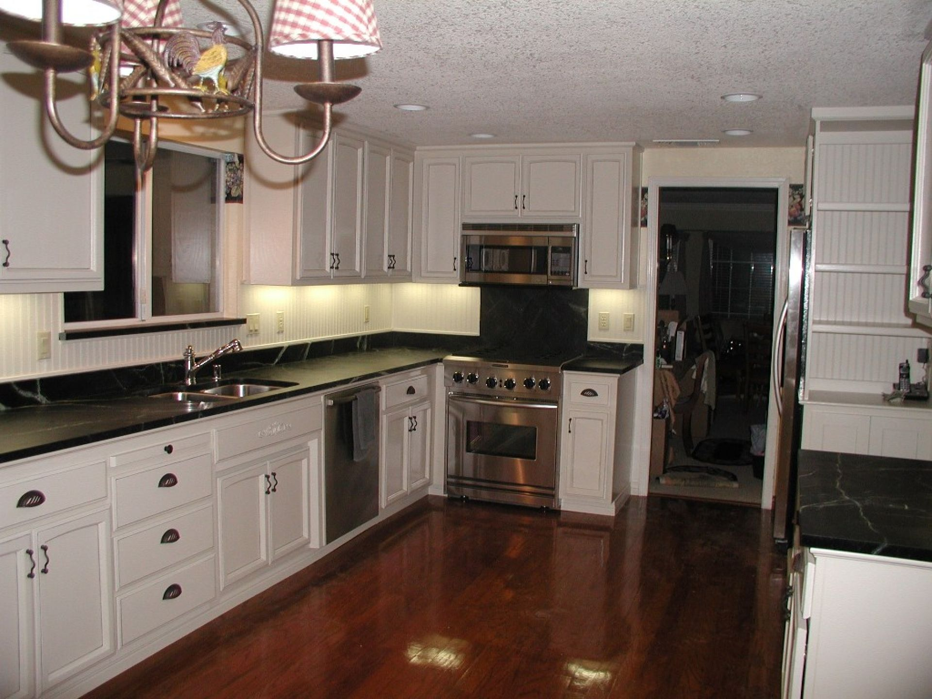 Dark hardwood kitchen floor feat white cabinets and black for Kitchen cabinets with dark floors