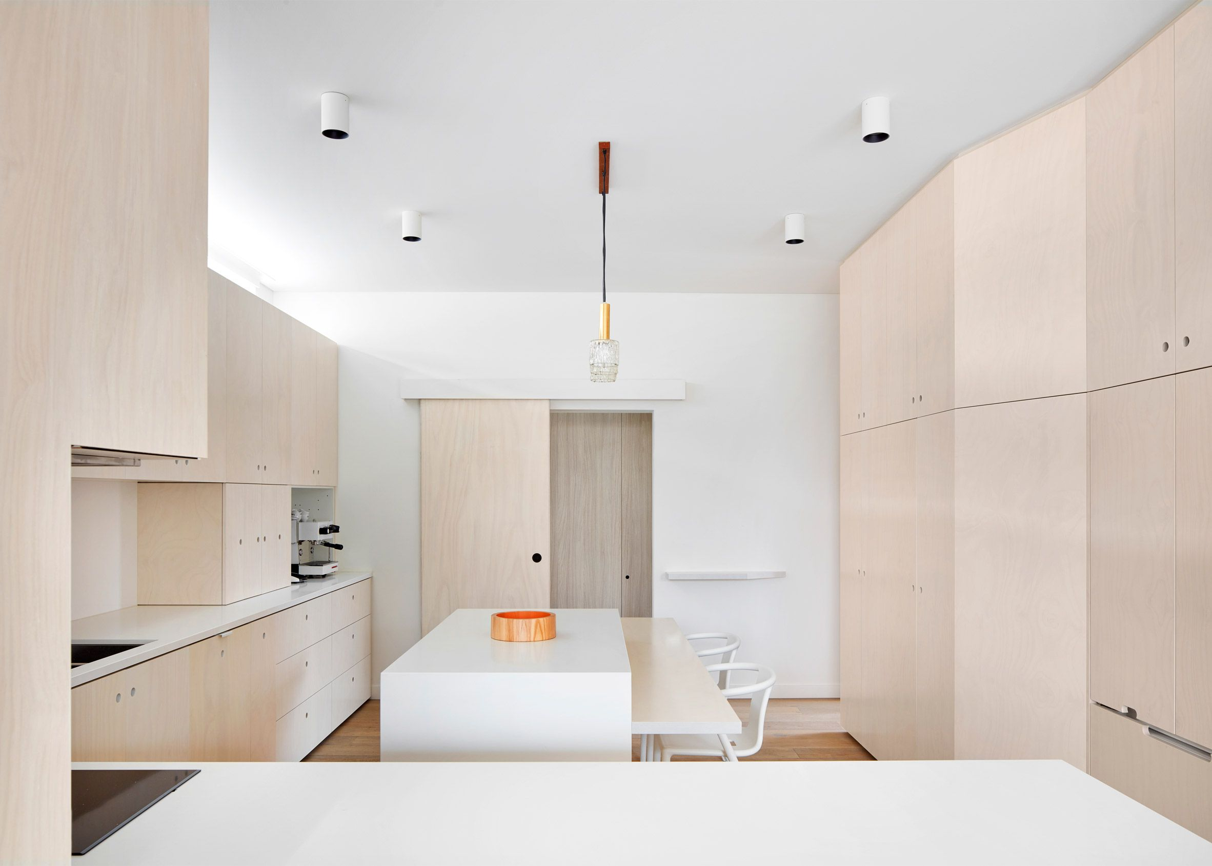 The kitchen of this house features contemporary cabinets fronted by ...