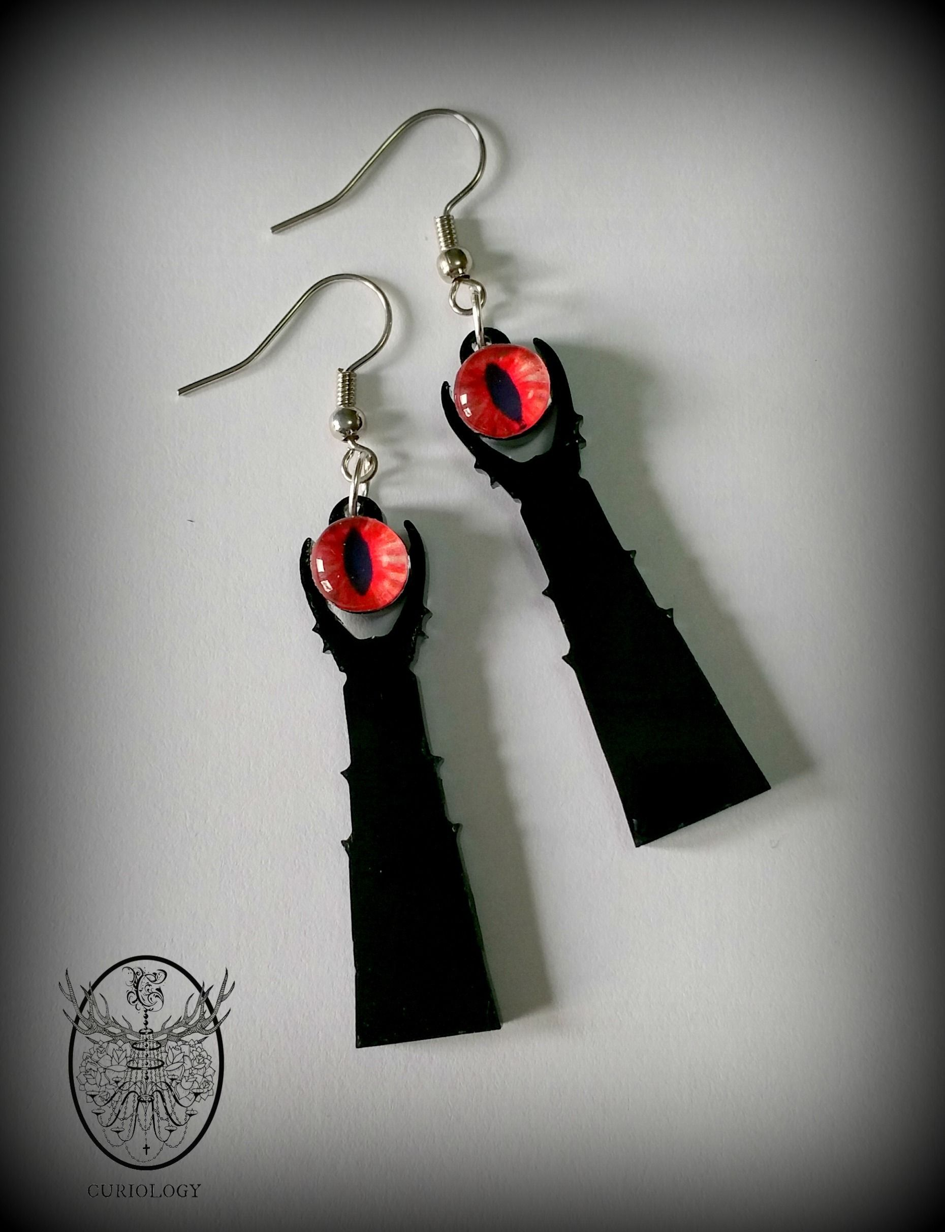 """""""Then at last his gaze was held: wall upon wall, battlement upon battlement, black tower of adamant, he saw it: Barad-dûr, Fortress of Sauron. All hope left him.""""5cm tall laser cut gloss black acrylic earrings, with tiny 8mm glass domes with the Eye of Sauron.Worn on nickel free silver or black ear hooks.As all items are made to order, please allow 3-5 working days for your item to dispatch. An email will be sent to you when your order is on the way. We shi..."""