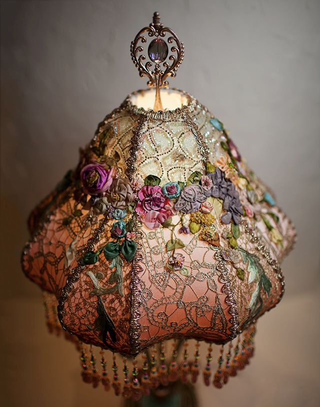 Victorian Lampshade with Antique French Embroidery. The shade is turban style and is dyed pale blue to soft champagne pink and is then overlaid with antique gold and silver metallic laces and 1920s sequin net. The shade is overlaid with a cascading collection of antique silk ribbon roses and flowers. The flowers are from the artist's personal collection accumulated over years. Hand beaded fringe in matching tones adorns the bottom and a finial with a glass center tops the lamp.