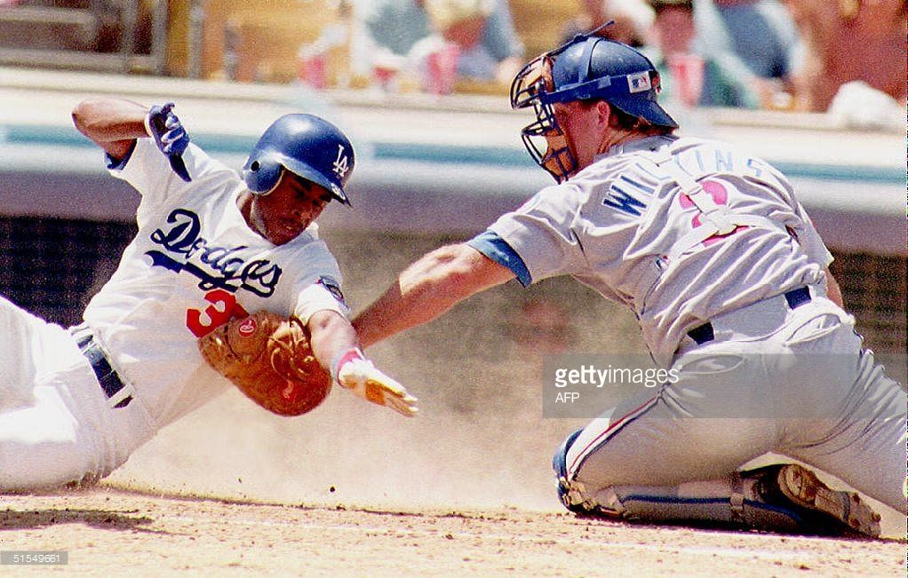 Los Angeles Dodgers Jose Offerman (L) is tagged out by Chicago Cubs catcher Rick Wilkins (R) before he can touch home plate 23 August 1992 in the third inning. The Cubs defeated the Dodgers 4-2 to sweep the three-game series.