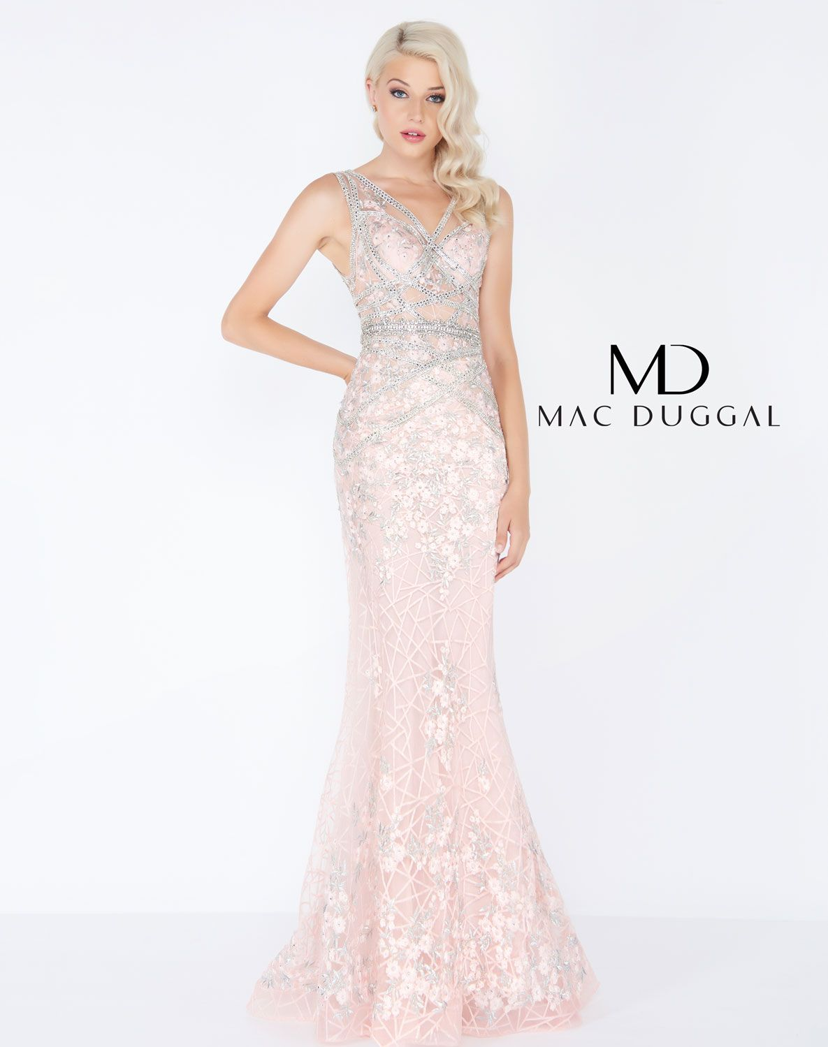 0b3ce170510 Form fitting blush prom dress with criss-cross beading and illusion bodice.  This elegant lace gown is accented with floral embroidery that gives way to  a ...