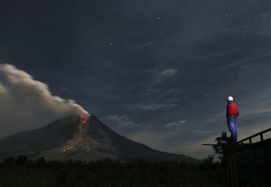 A man looks at Mount Sinabung spewing ash from Jraya village in Karo district, Indonesia's North Sumatra province, January 13, 2014. REUTERS...