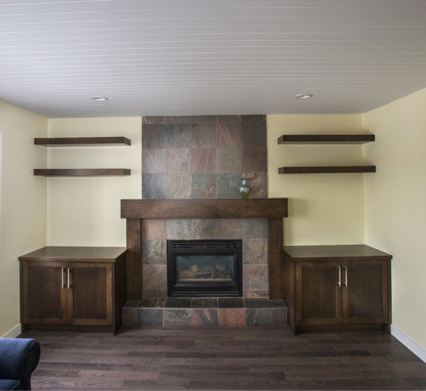 stunning wood mantle and cabinets by envision custom renovations