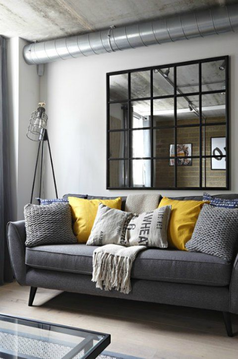 A Gray Industrial Living Room With A Gray Sofa And Yellow