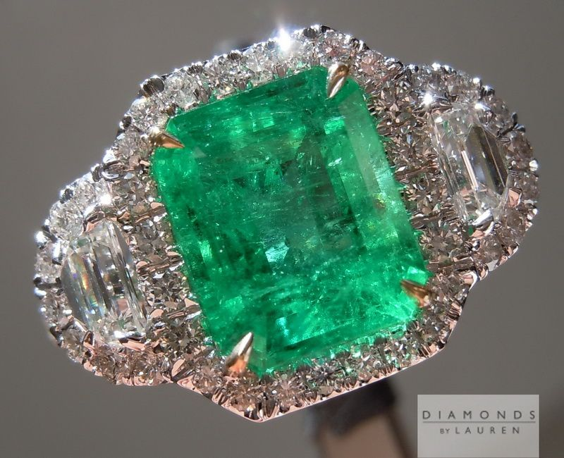 The emerald center stone stands out beautifully in this hand forged three stone halo ring.