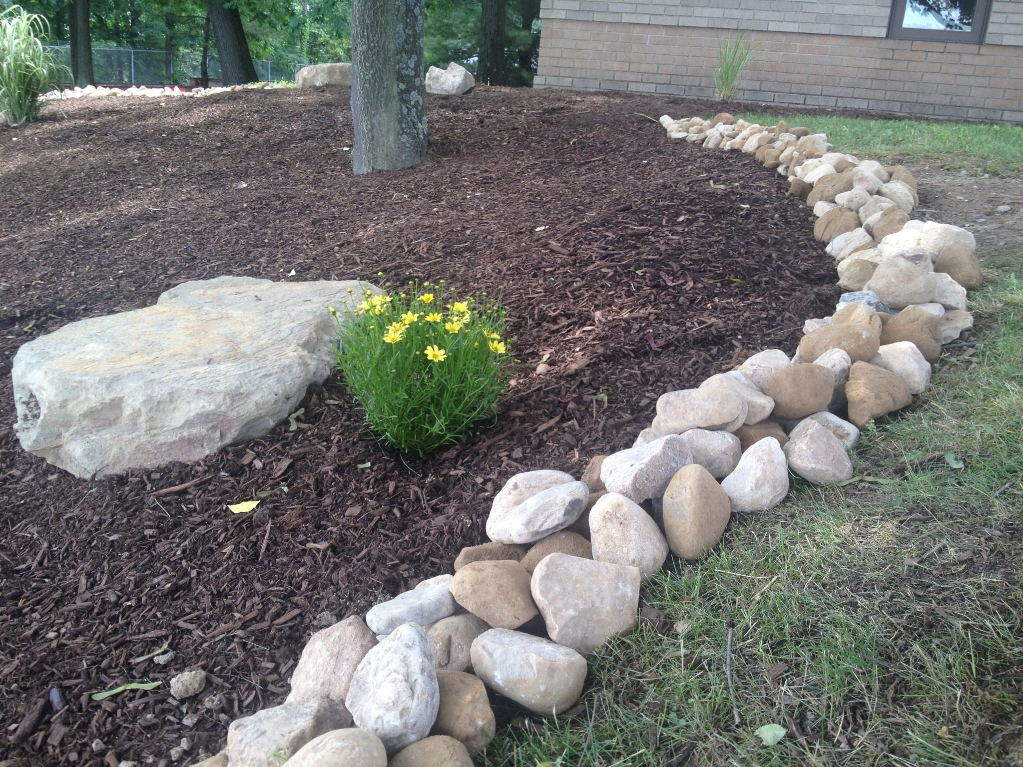 Large river rock makes an incredible border river rock landscaping landscaping around trees front