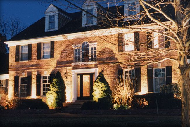 Stately Brick Home Illuminated By Uplighting And Shadowing