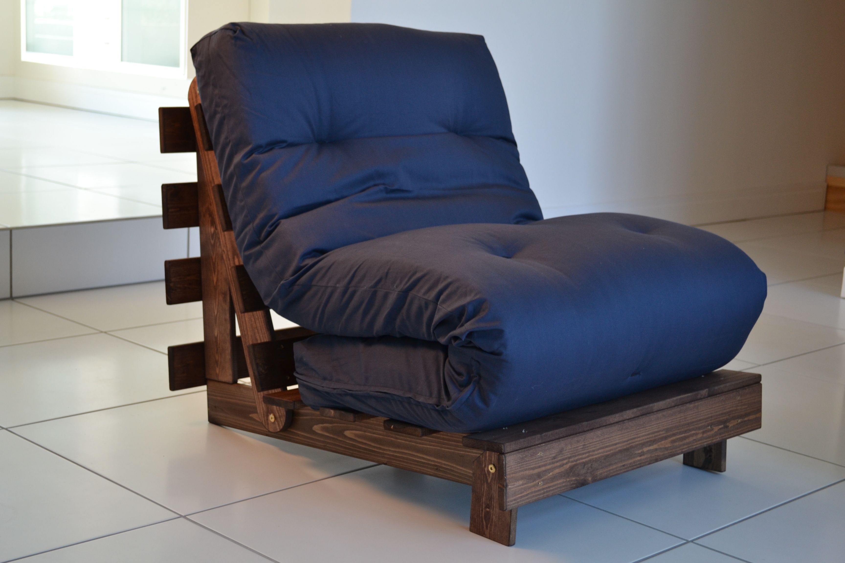 A blue futon folded up onto a brown DIY wood pallet chair