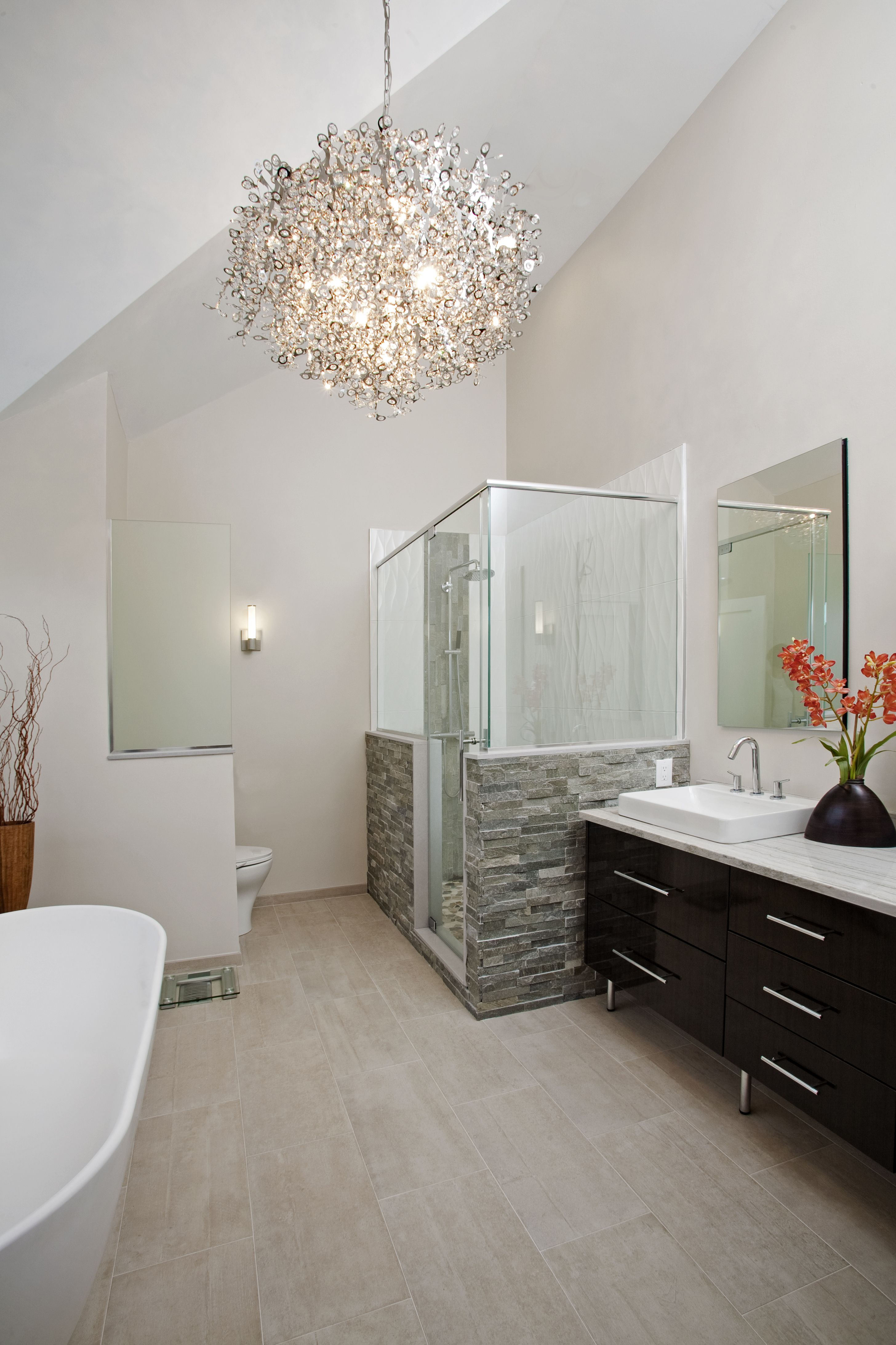 The vaulted ceiling and contemporary chandelier really make a statement in this spa master for Contemporary bathroom chandeliers