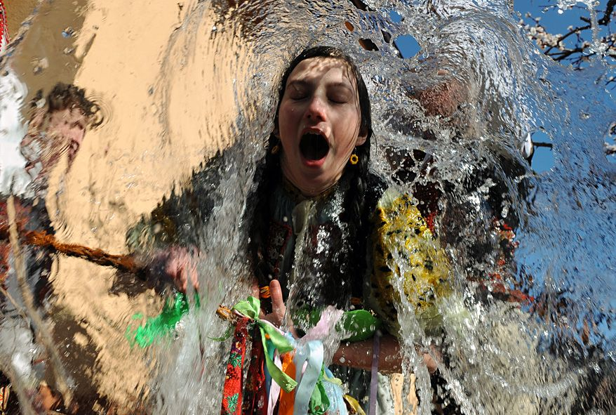 Young Slovaks dressed in traditional costumes throw a bucket of water at a girl as part of Easter celebrations in the village of Trencianska Tepla, north of Bratislava. (AFP).  Really, so gad my grandparents didn't bring this custom to Nebraska!