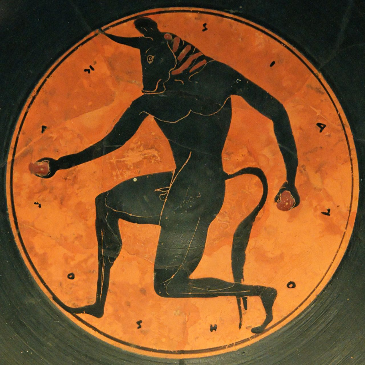 "The Minotaur.  The surrounding description reads ὁ παῖς καλός (""The boy is handsome/beautiful"").  Tondo of an Attic black-figure kylix,  attributed to the Painter of London E4; ca. 515 BCE.  Now in the National Archaeological Museum of Spain, Madrid.  Photo credit: Marie-Lan Nguyen/Wikimedia Commons."