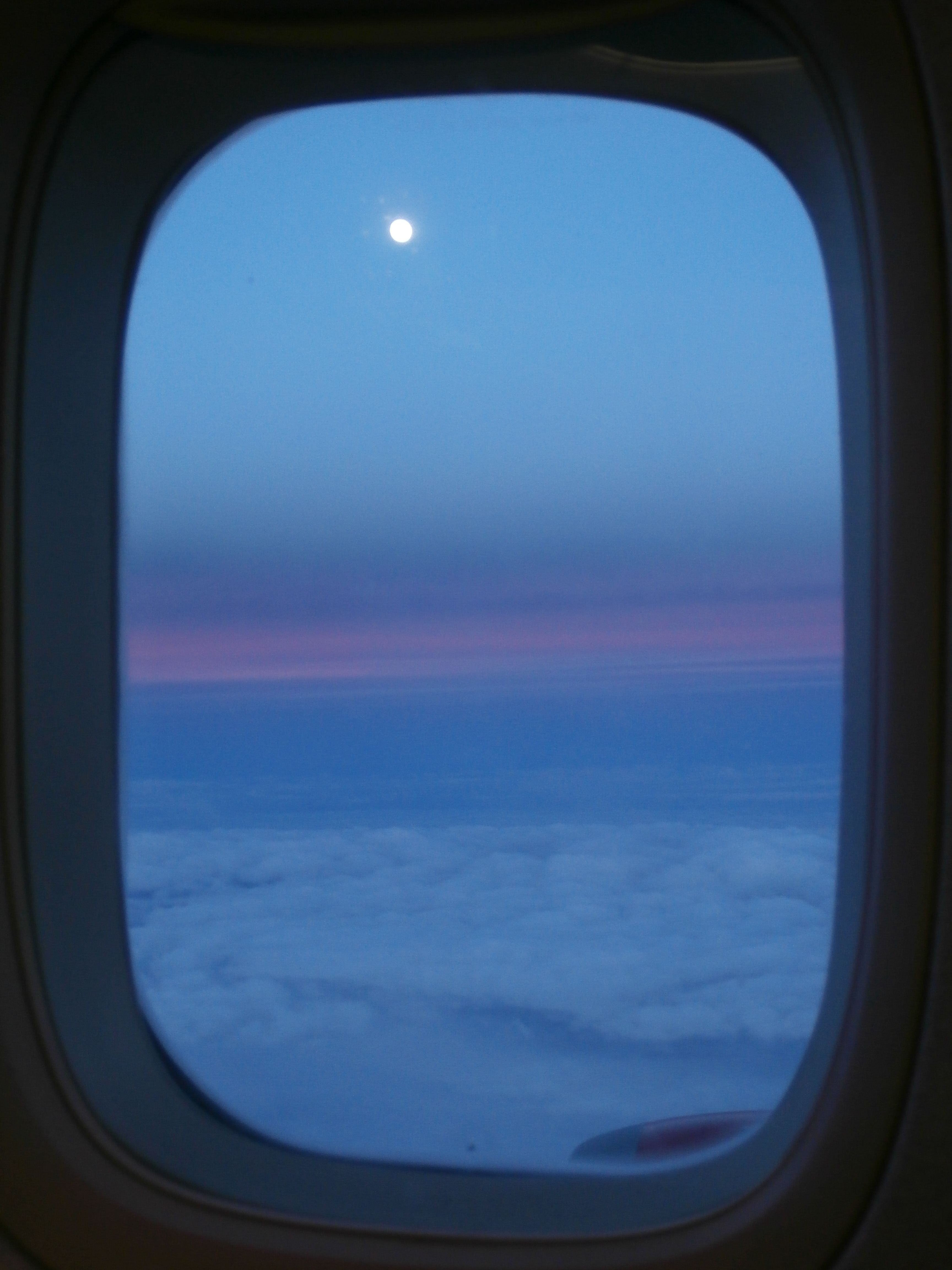 TMN© Just because you can...  A shot from the plane window, setting sun and rising moon on only fluffy clouds.