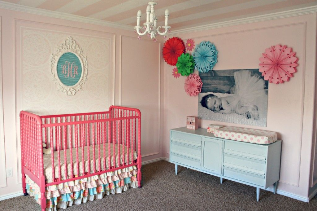 The over-sized photo canvas and paper flowers make such an impact in this pink nursery.
