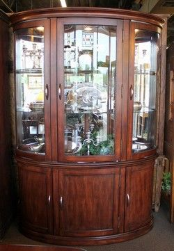 Curved front china cabinet with lighted glass door hutch. Base has ...