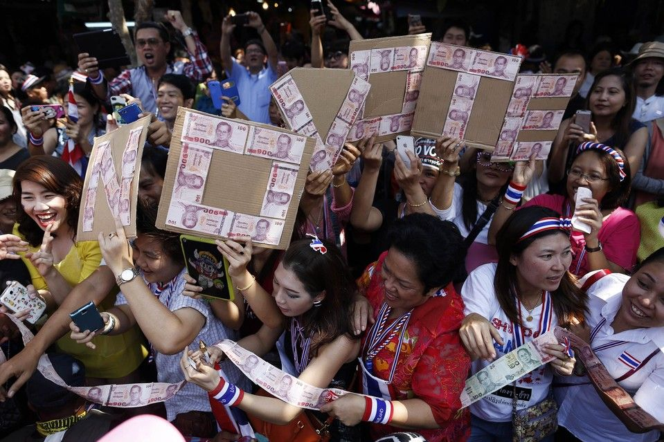 Damir Sagolj/Reuters STREET SIGNS: Protesters spelled 'No Vote' with Thai baht bank notes as they marched through Bangkok Friday. Authorities might close polling booths if violence erupts during Sunday's disputed election.